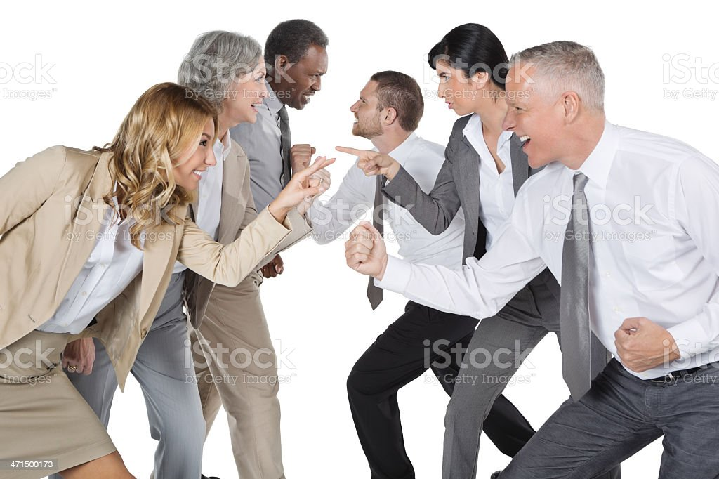 Two diverse business teams 'arguing' competitively; studio shot royalty-free stock photo