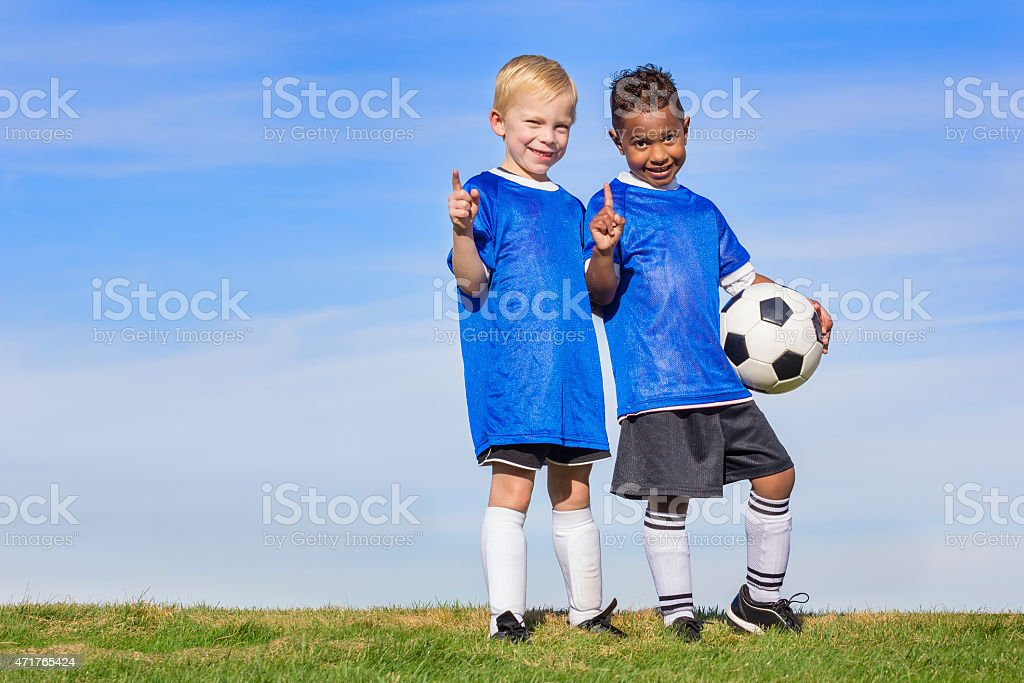 Two diverse young soccer players showing No. 1 sign stock photo