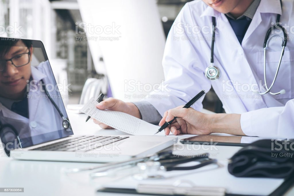 Two doctors being discussing patient history in an office pointing to a clipboard with document paper as they make a diagnosis or recommend on treatment stock photo
