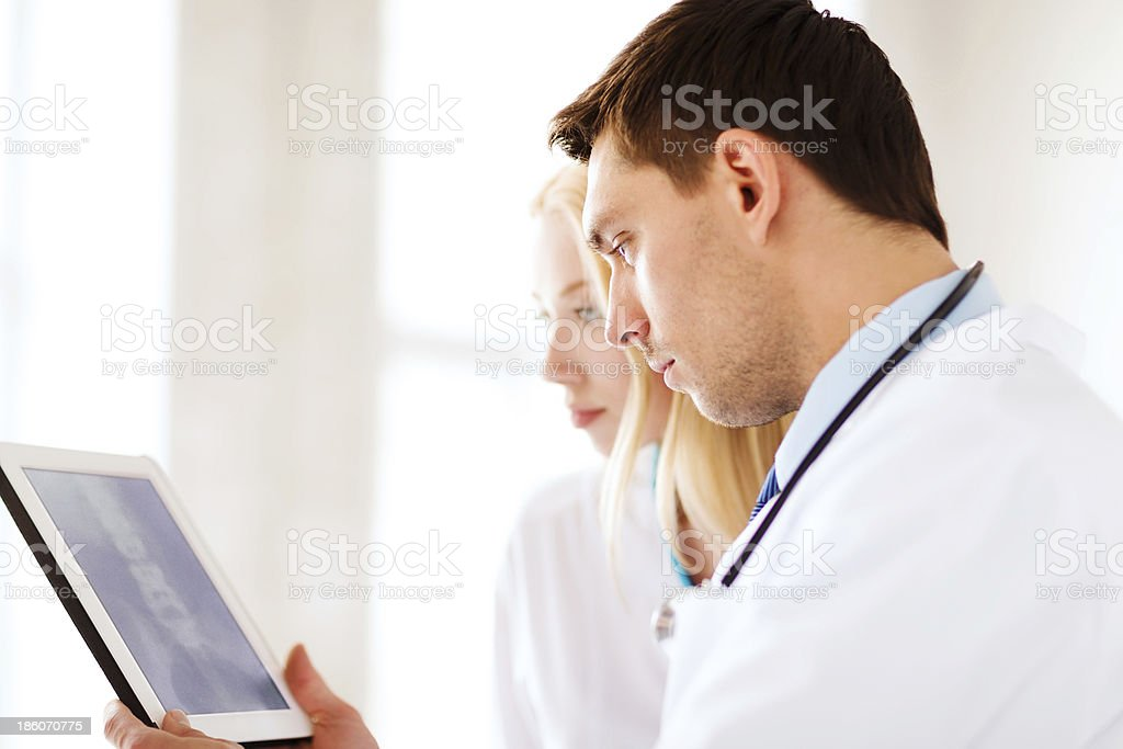 two doctors looking at x-ray on tablet pc stock photo