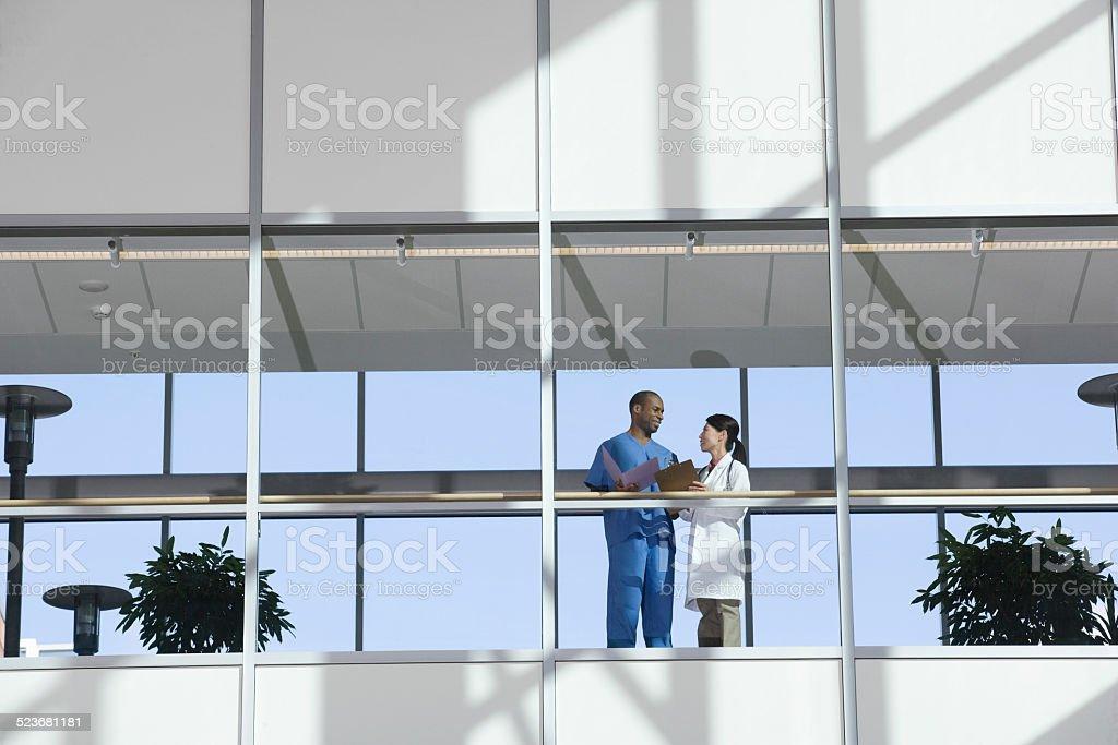 Two Doctors Talking in Corridor stock photo