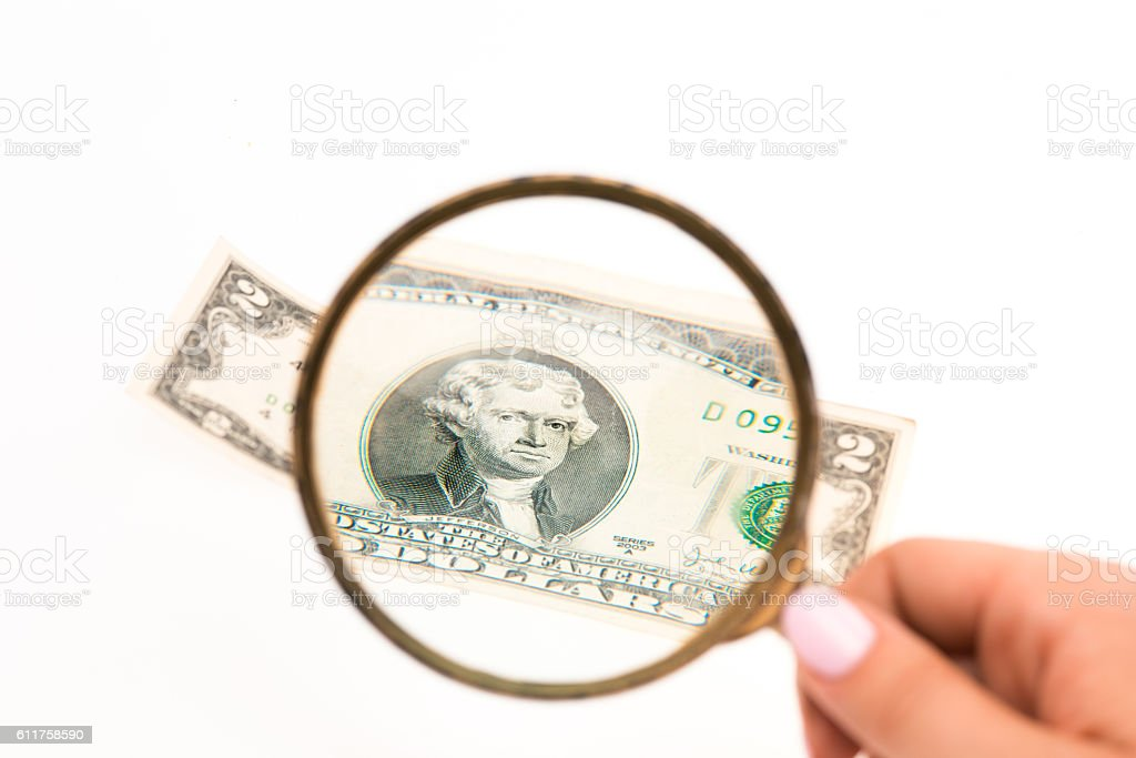 Two dollars bill and magnifying glass stock photo