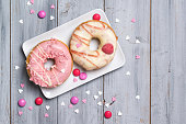 Two donuts decorated with smarties and sprinkles hearts