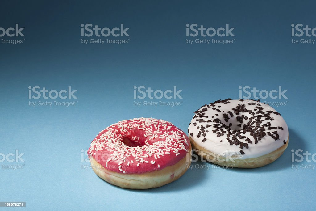 two donuts with red and white icing isolated on blue royalty-free stock photo