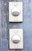 Two doorbell ring button on concrete wall
