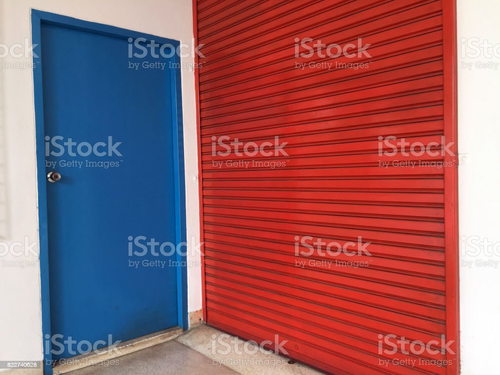 Two doors next to each other, small blue wooden door and big red metal door. stock photo