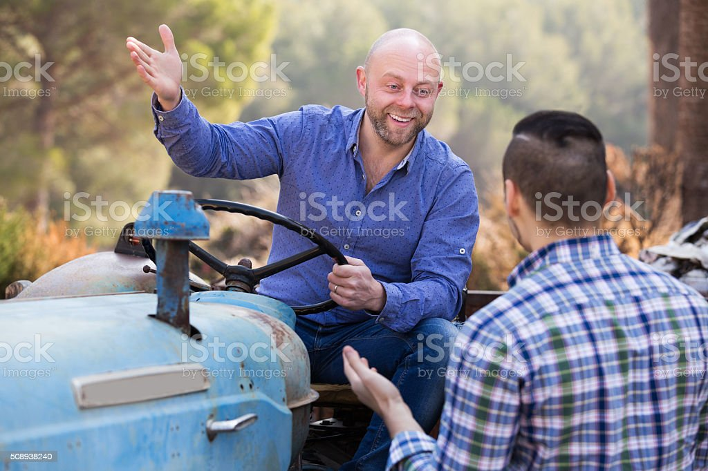 Two drivers working with tractor stock photo