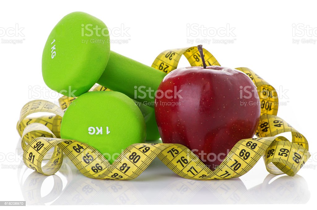 Two dumbbells, red apple, measuring tape. stock photo