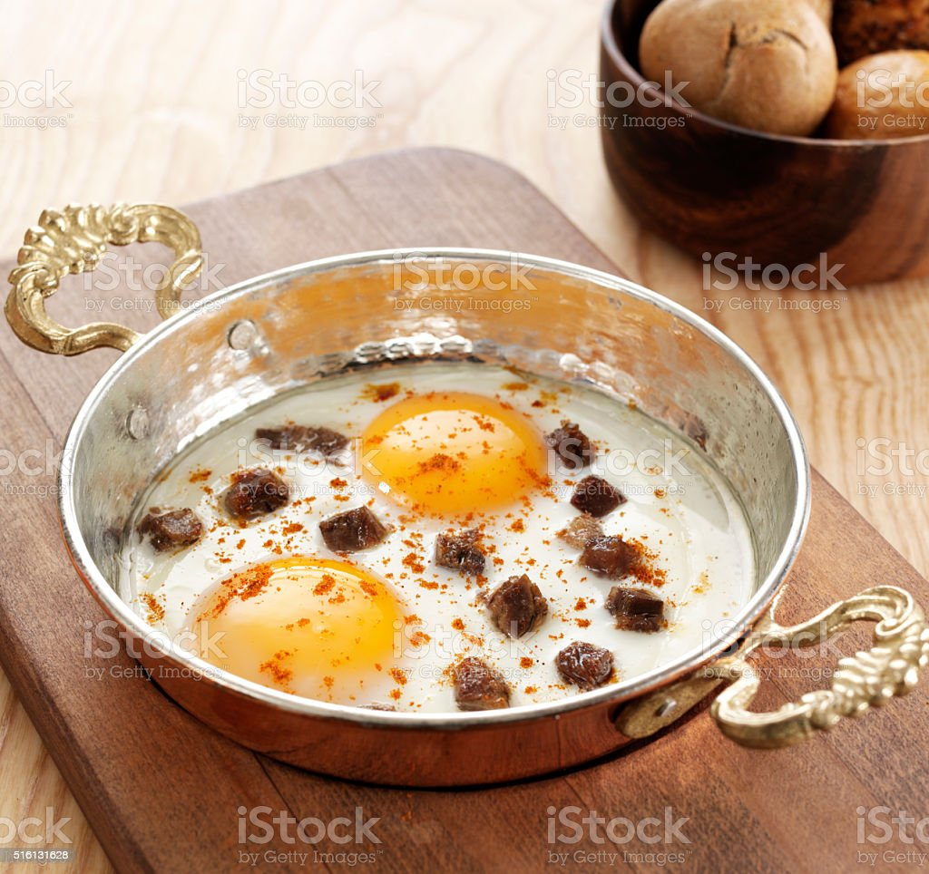Two eggs and meat pieces frying stock photo