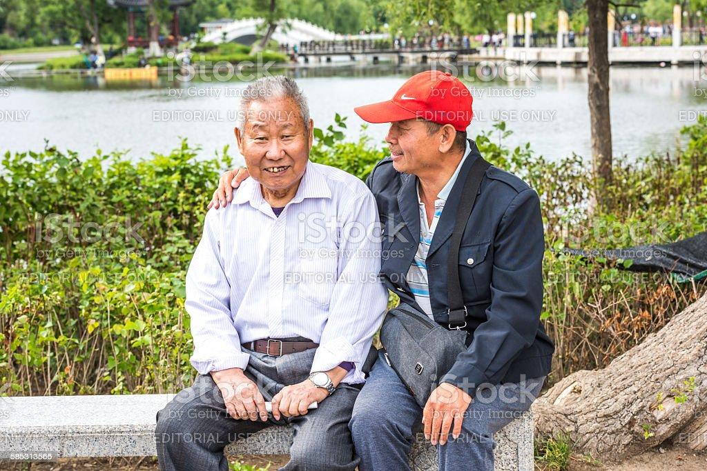 Two elderly Asian men sitting on the stone bench stock photo