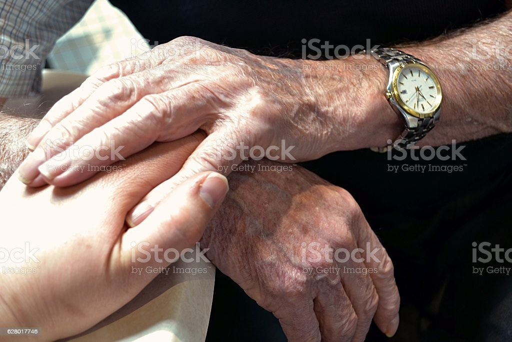 Two elderly hands holding onto a younger hand stock photo