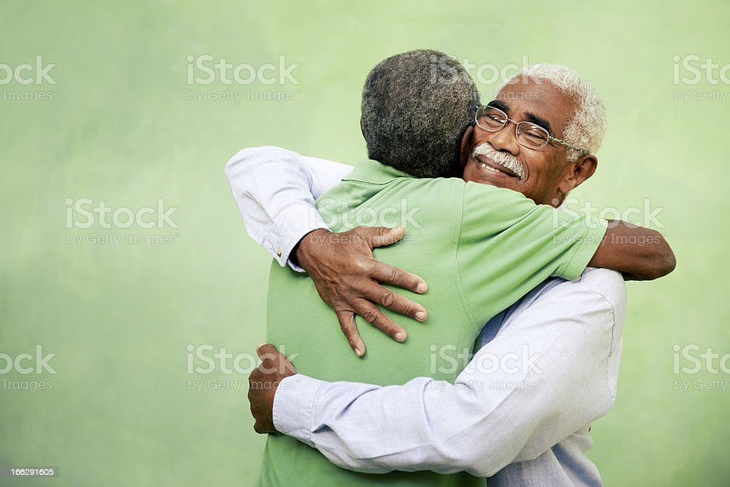 Two elderly men hugging on a green background stock photo