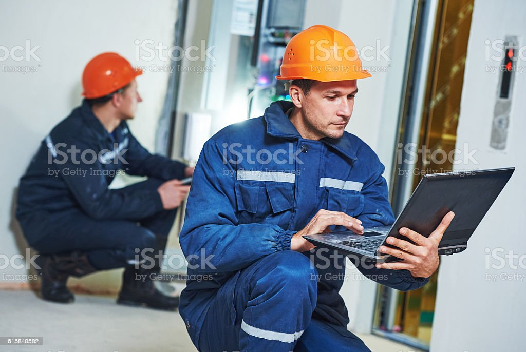 Two electrician works with electronic equipment stock photo