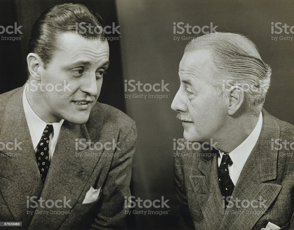 Two elegant men talking in studio, (B&W), close-up stock photo