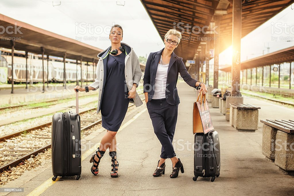 Two elegant woman with suitcase posing on the railway station stock photo