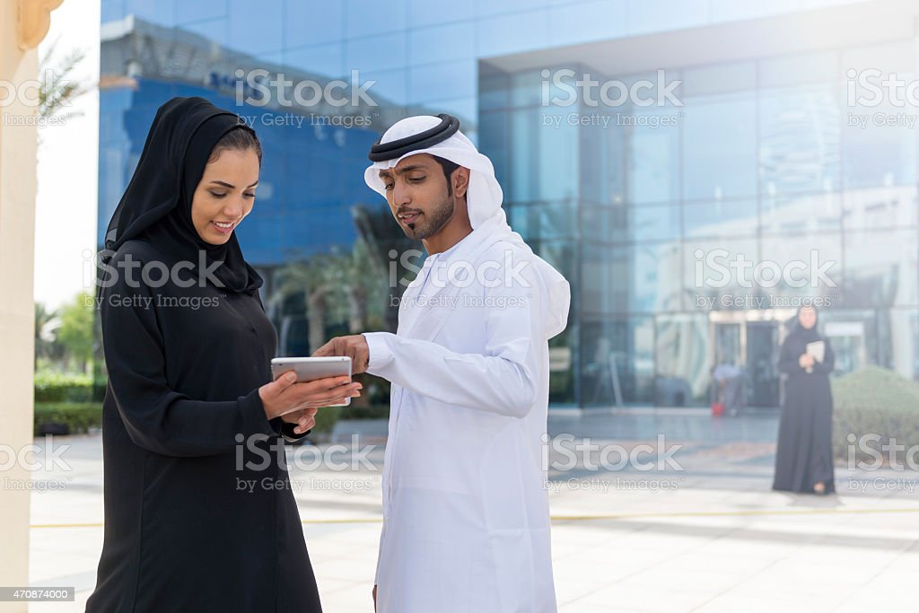 Two Emarati Business people talking outside the office. stock photo