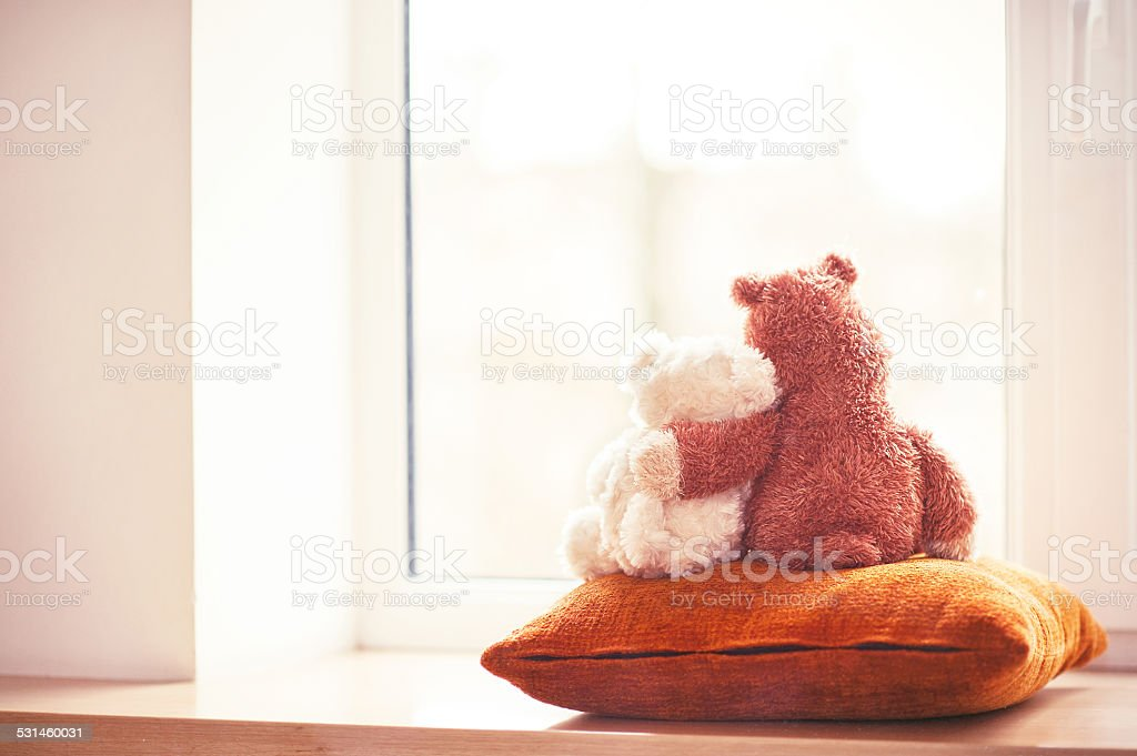 Two embracing teddy bear toys sitting on window-sill stock photo