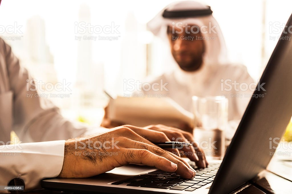 Two Emirates business men filling documents in a cafe stock photo