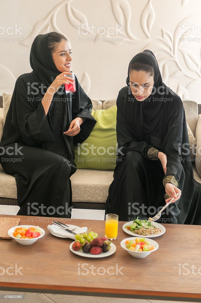 Two Emirati Women in Black Abaya and Hijab Eating Lunch stock photo