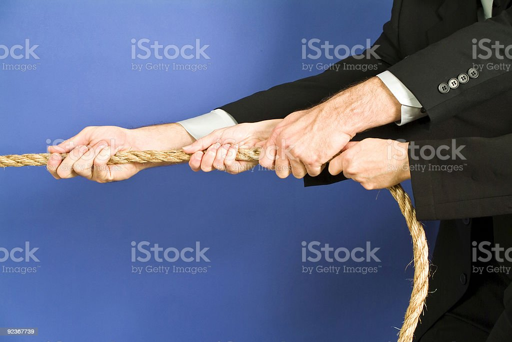 Two employees in black suits tugging on one side of a rope royalty-free stock photo