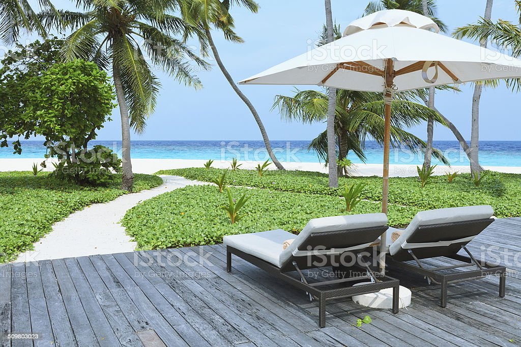 Two empty sunbed on the beach stock photo