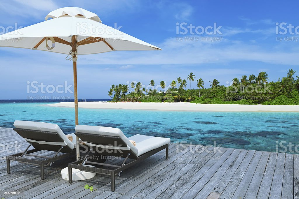Two empty sunbed on the water villa balcony stock photo