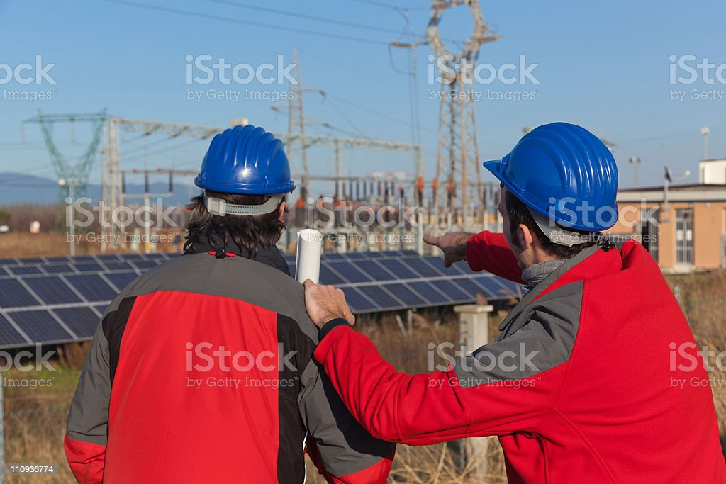 Two Engineers at Work In a Solar Power Station royalty-free stock photo
