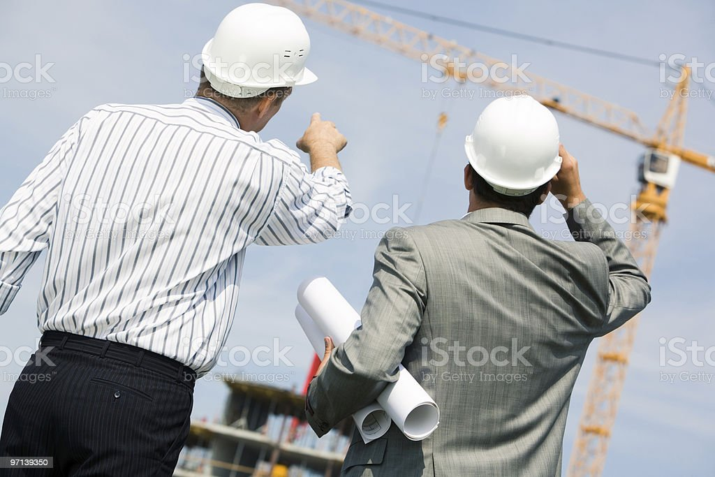 Two engineers examining construction progress on site royalty-free stock photo