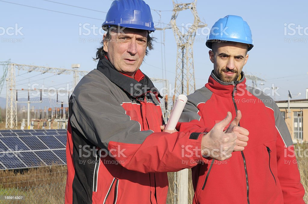 Two Engineers Giving OK in a Solar Power Station royalty-free stock photo