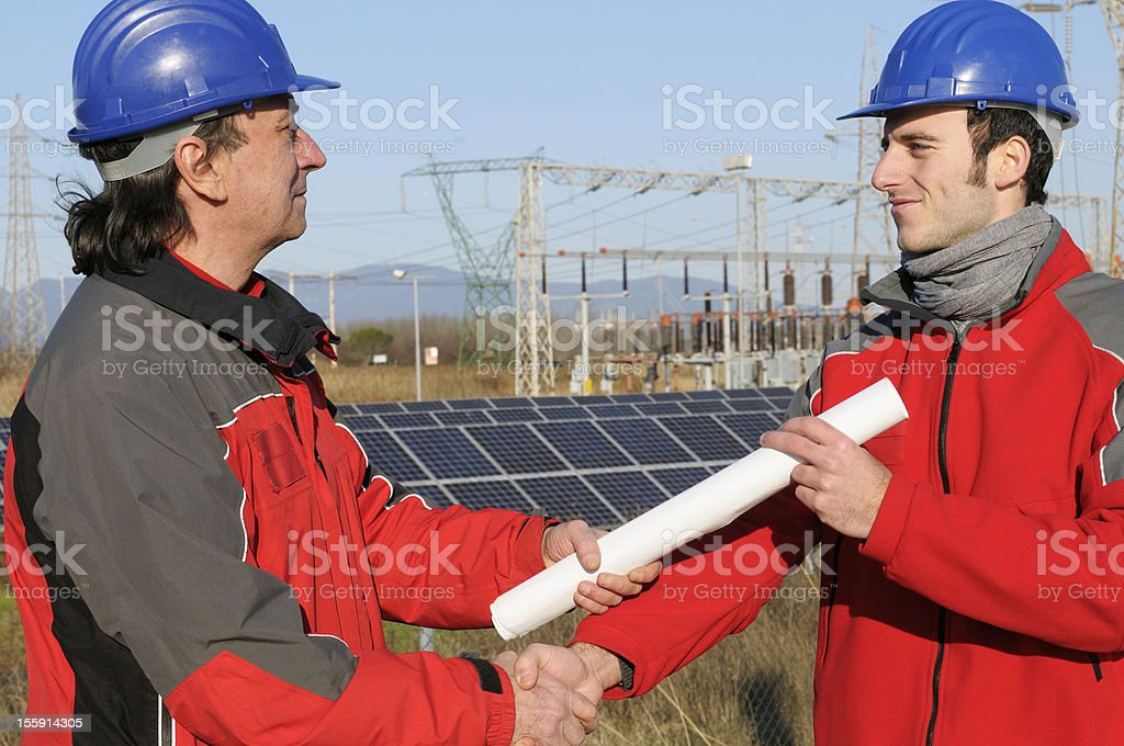 Two Engineers Handshaking in a Solar Power Station royalty-free stock photo