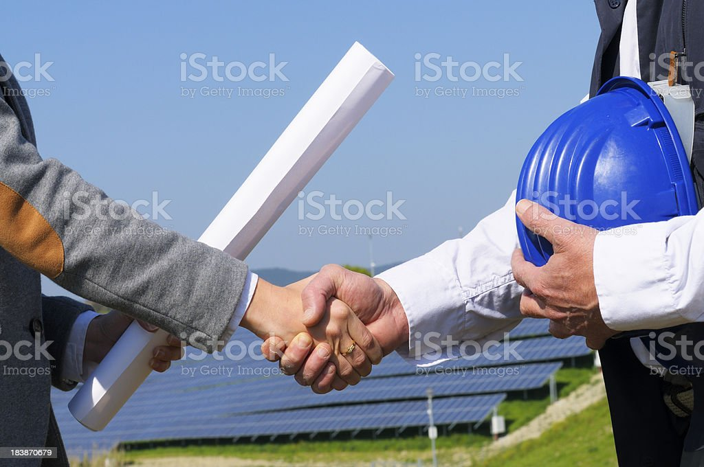 Two Engineers Handshaking in Solar Power Station royalty-free stock photo