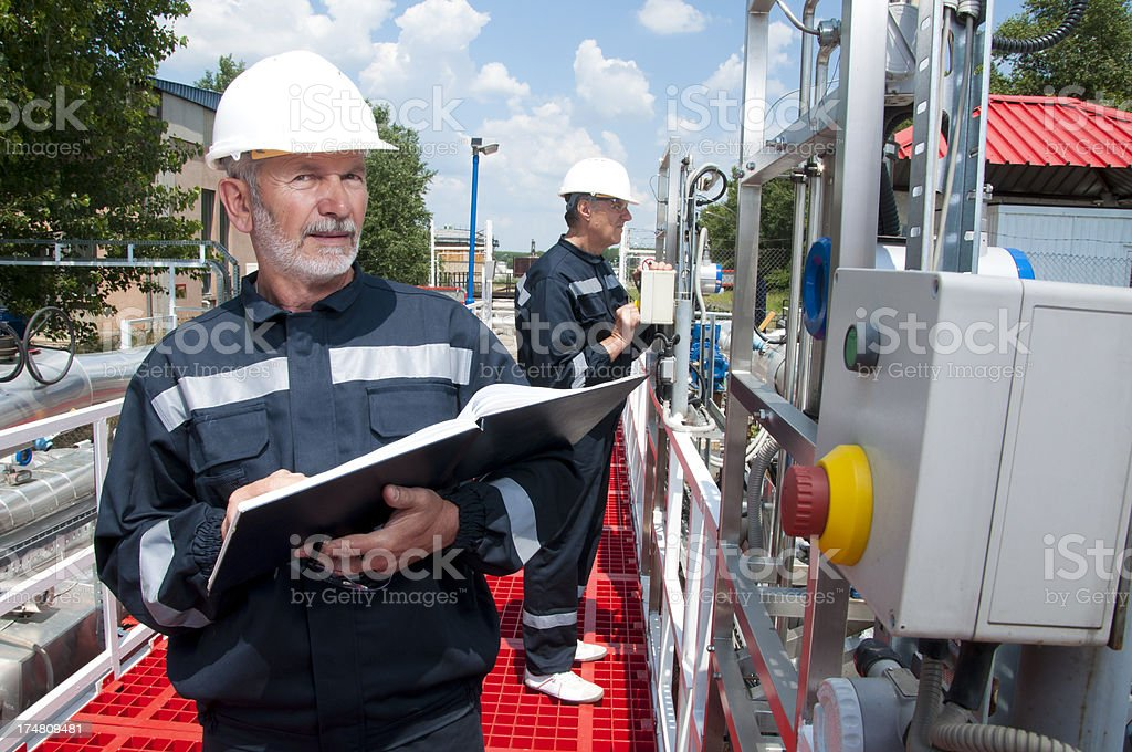 Two engineers overlooking oil pipeline royalty-free stock photo