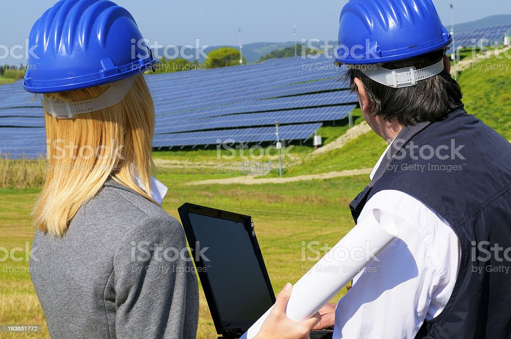 Two Engineers Planning PC in a Solar Power Station royalty-free stock photo