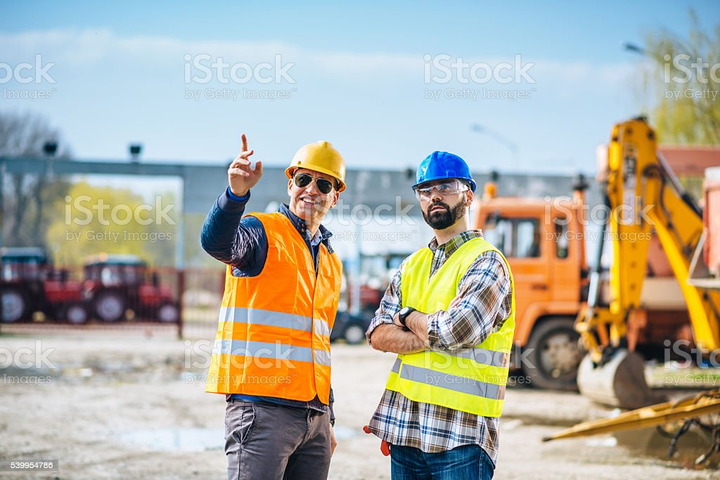 Two engineers posing near trucks and machinery on construction site stock photo
