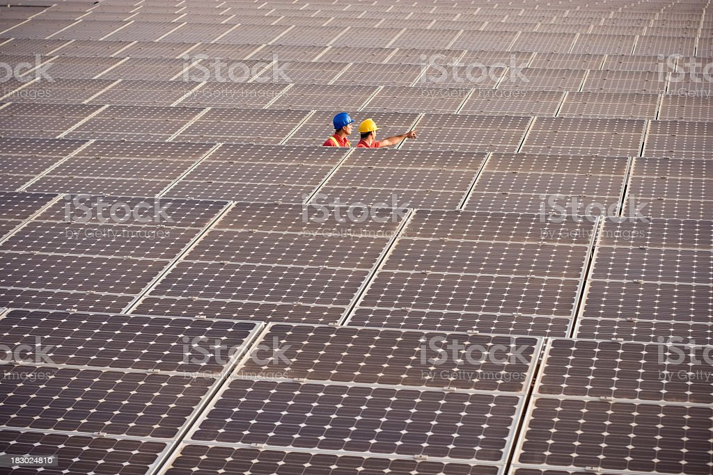 Two engineers working on solar panels royalty-free stock photo