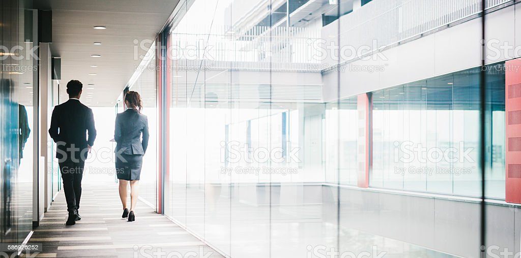Two Entrepreneurs Walking Down the Hallway stock photo