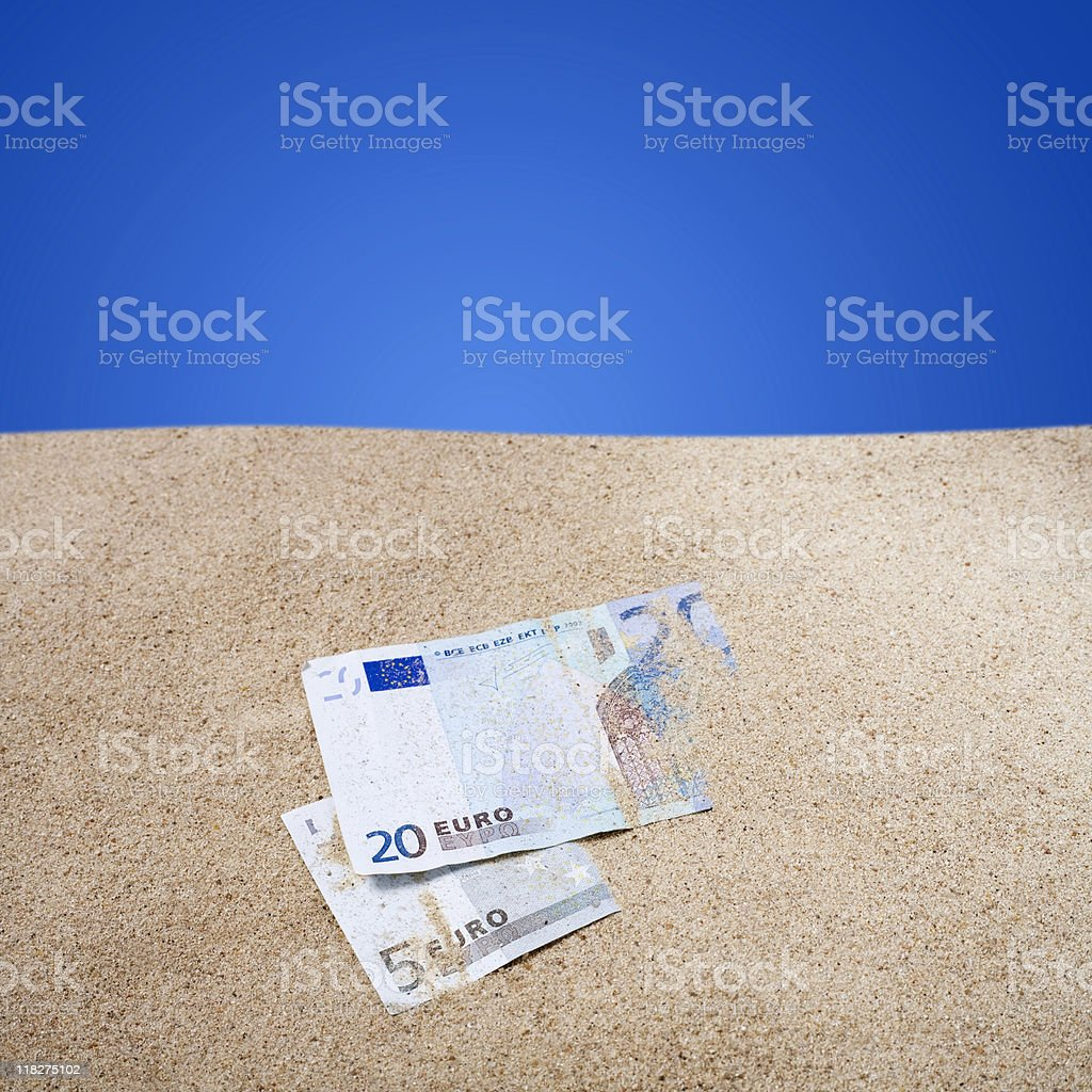 Two euro banknotes half buried in the sand stock photo