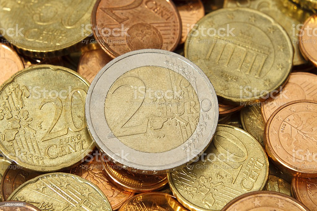 Two Euro coin on top of other Euros coins stock photo
