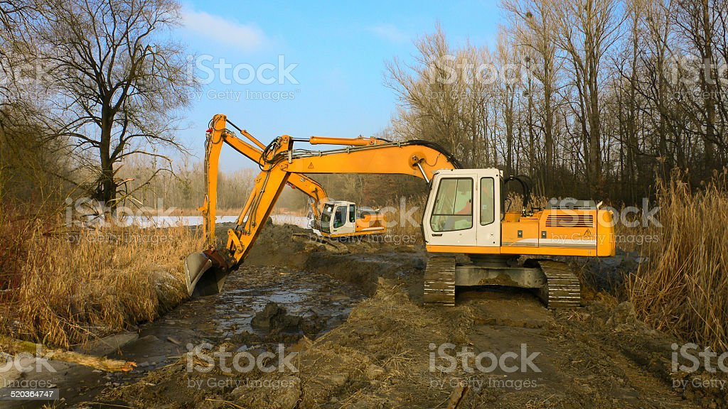 Two excavators digs inflow into lake for a fish pass stock photo