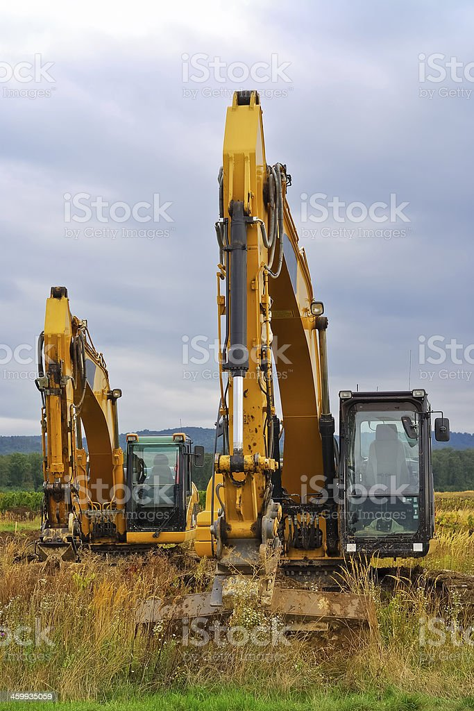 two excavators in the meadow at work stock photo