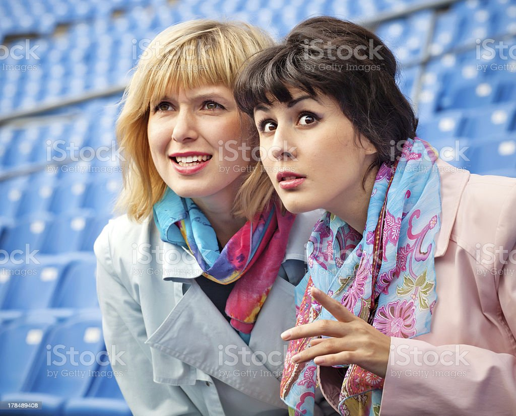 two excited  women fans watching  competition or concert in stad royalty-free stock photo