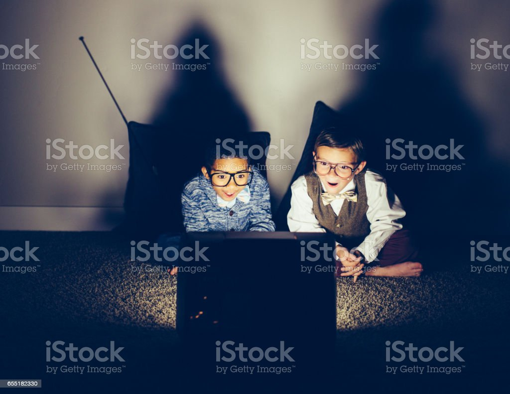 Two Excited Young Nerds Watching Late Night Television stock photo
