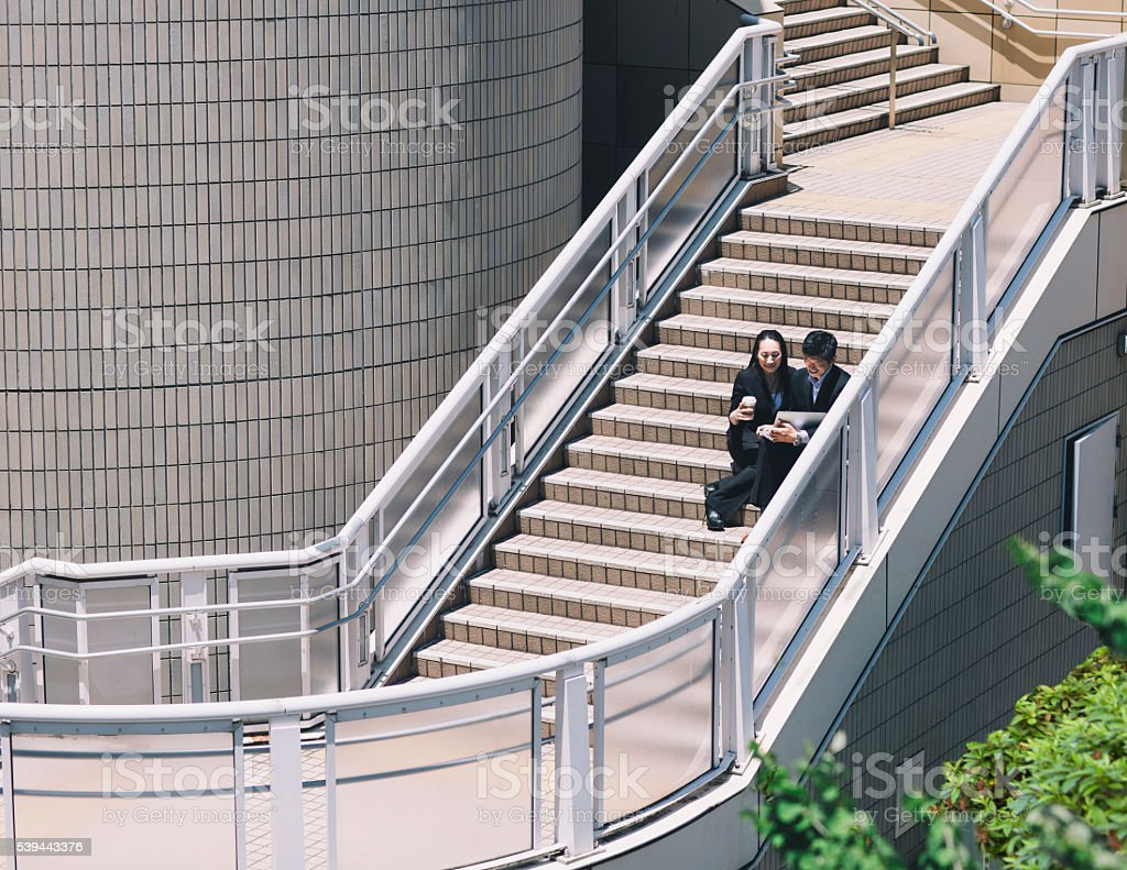 Two executives sitting on the staircase stock photo