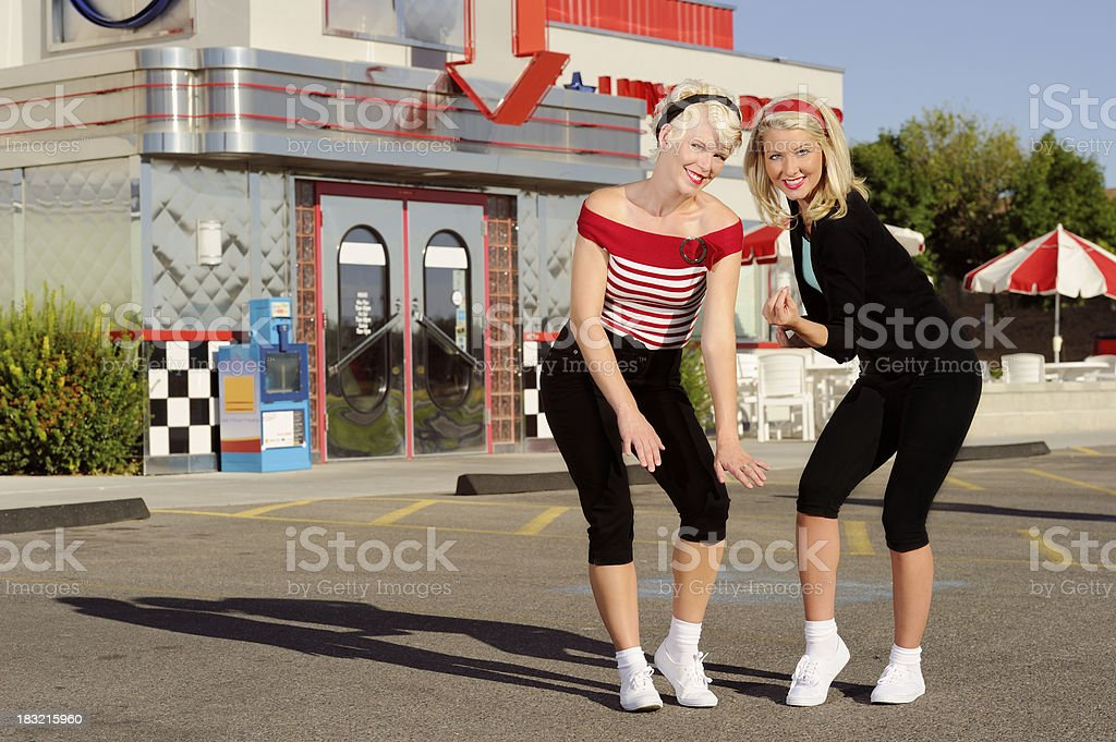 Two Fabulous 50's Women Dancing In Front Of Retro Diner stock photo