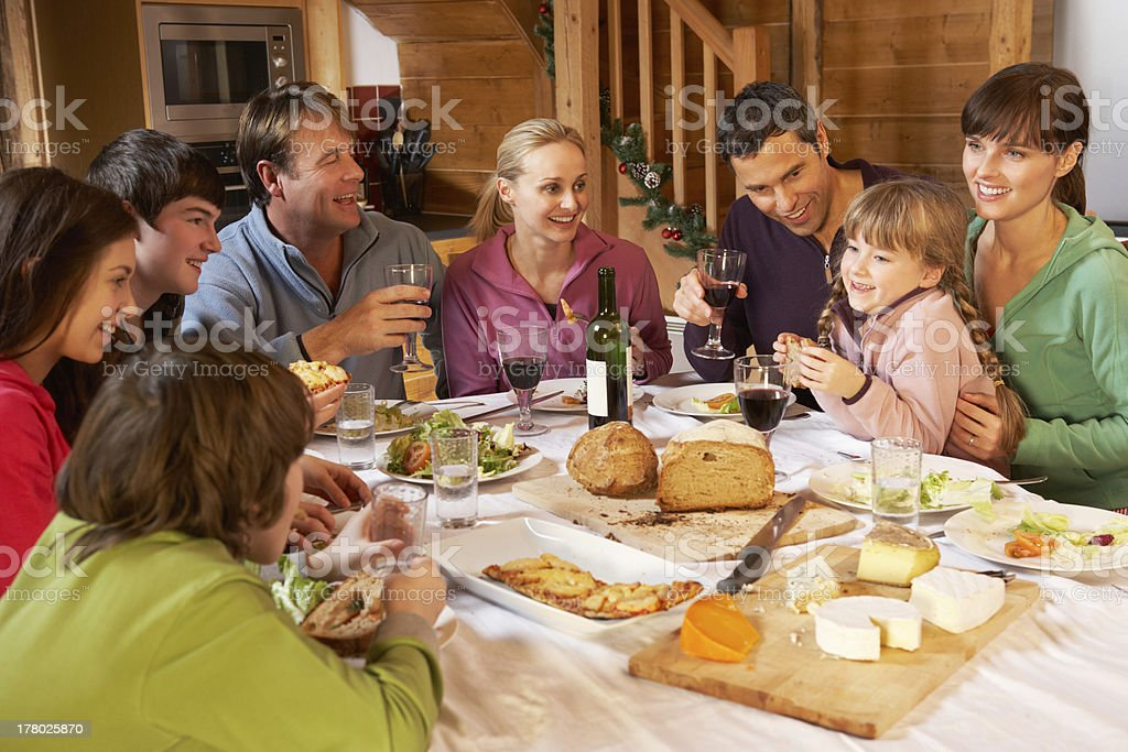 Two families enjoying a meal in an alpine chalet stock photo