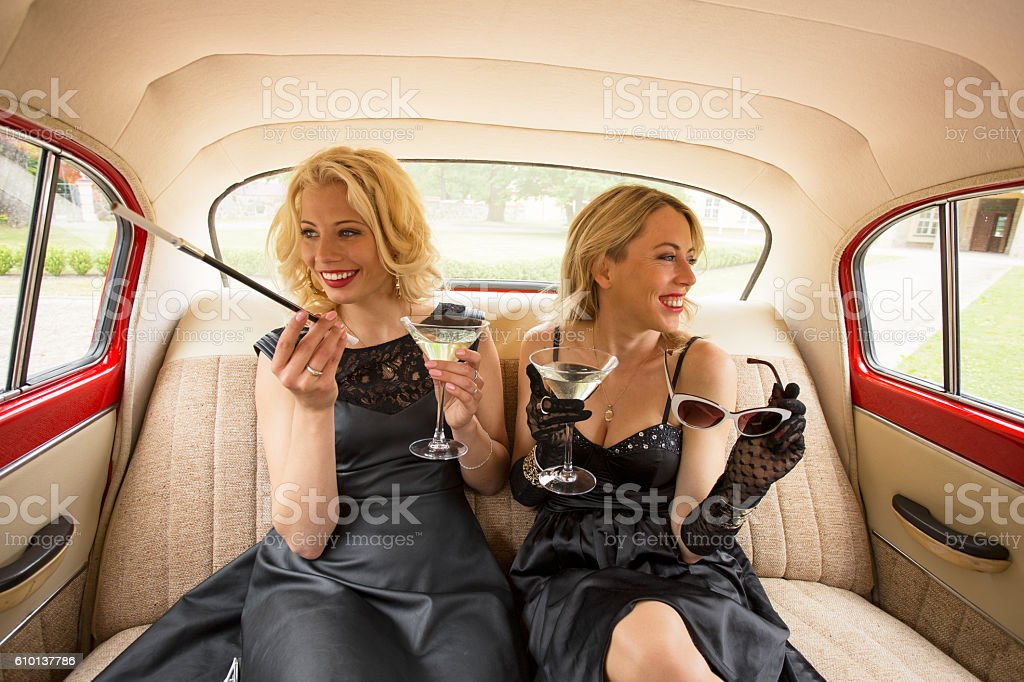 Two fancy woman sitting in retro car and enjoying life stock photo