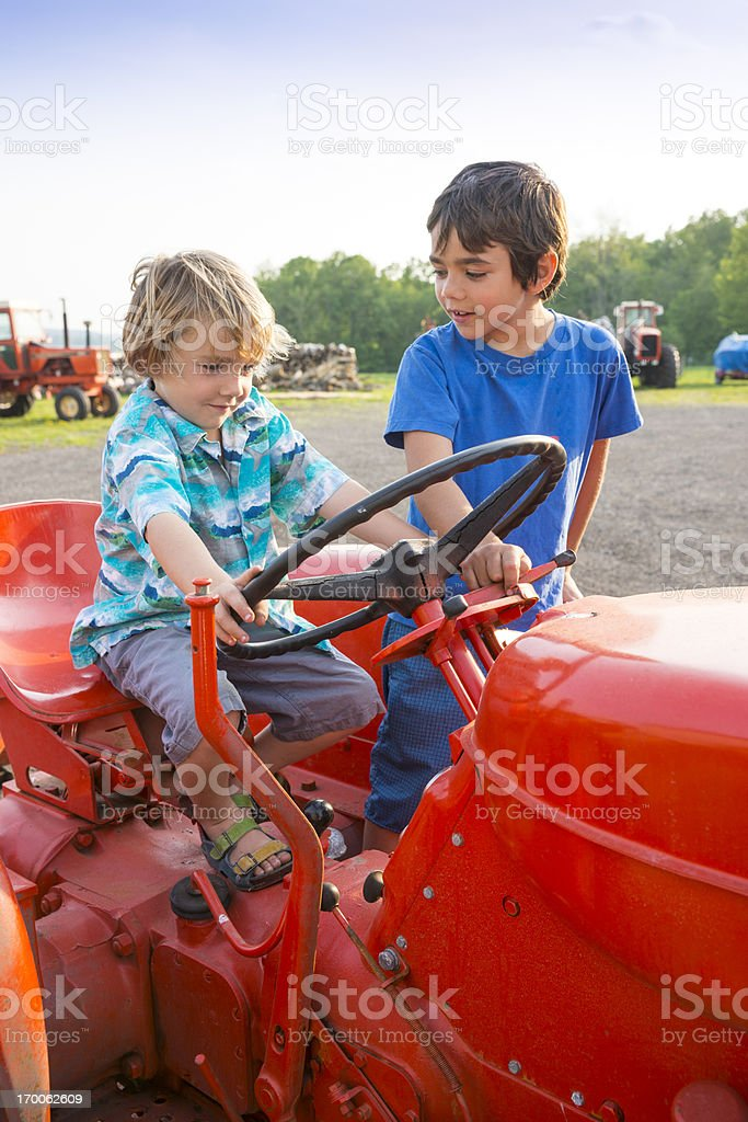 Two farm children on a tractor royalty-free stock photo