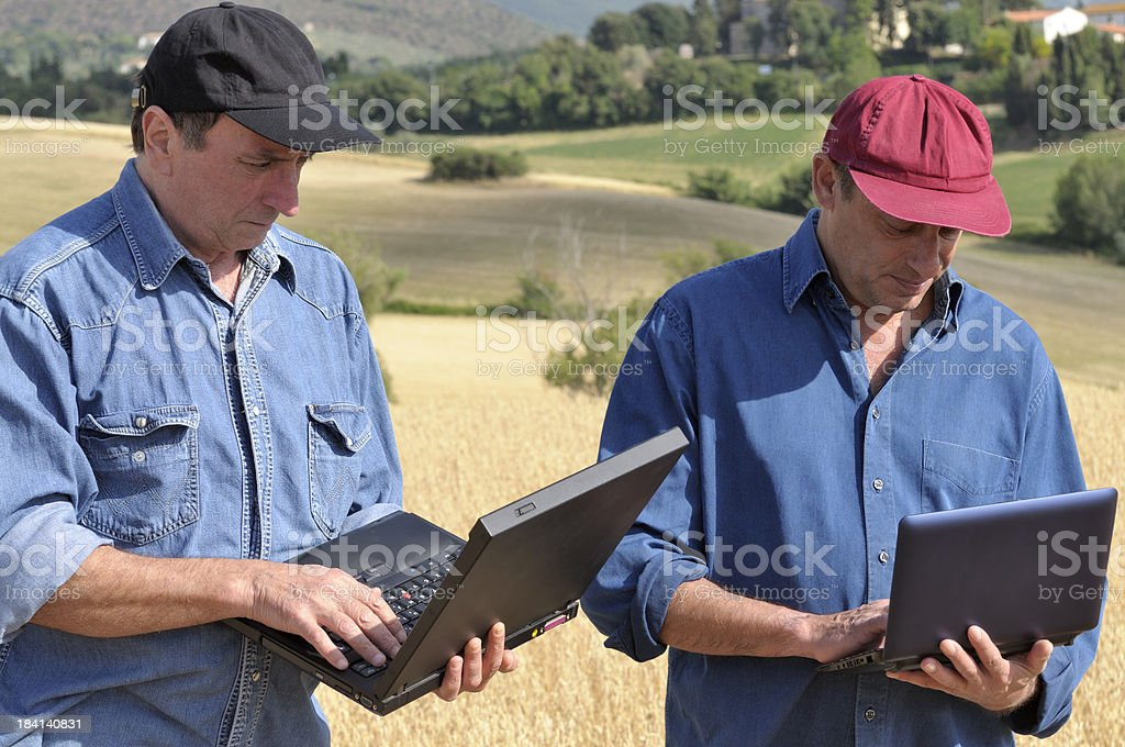 Two Farmers Planning PC in the Countryside royalty-free stock photo