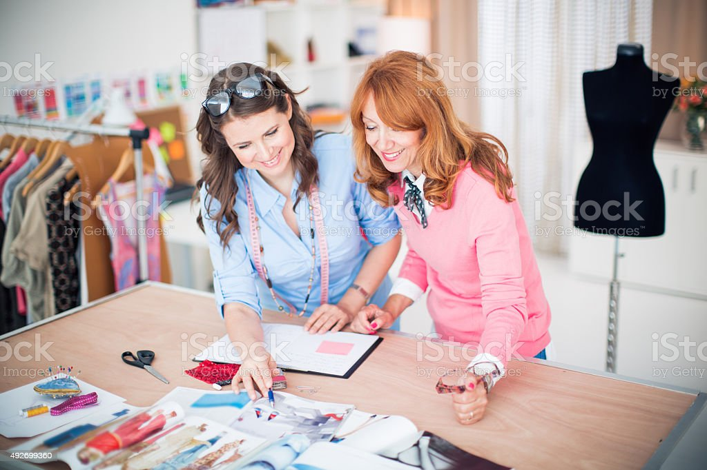 Two fashion designers discussing a design. stock photo