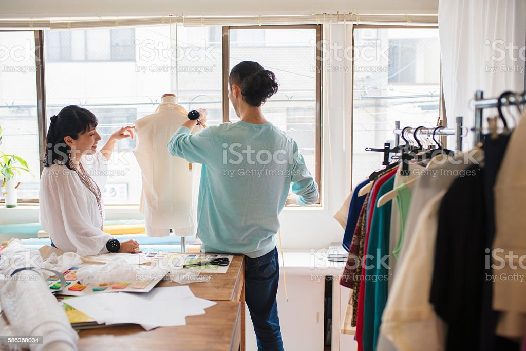 Two fashion designers taking measurements stock photo